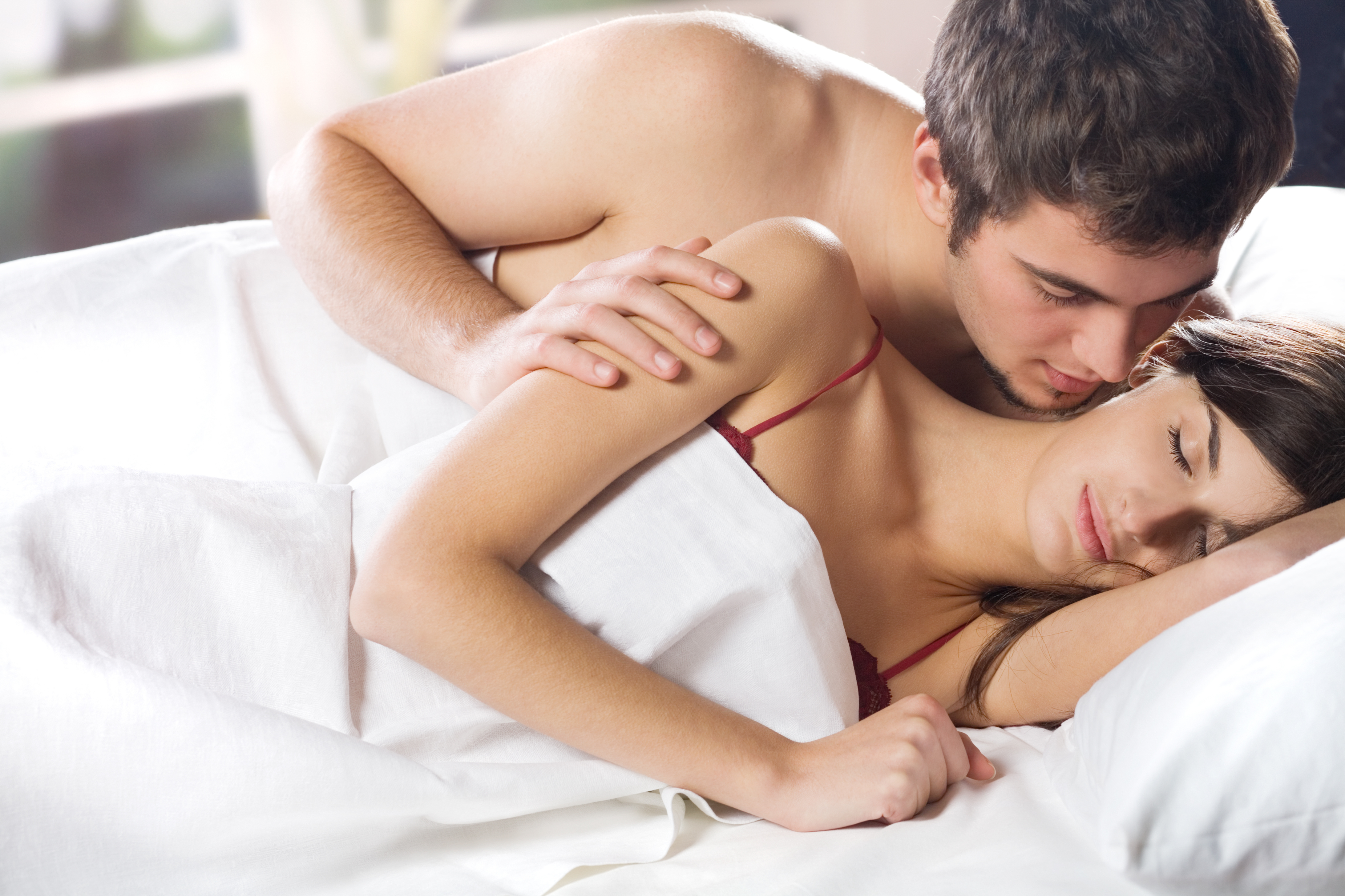 couple laying on white bed